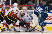 Markus Granlund #60 of the Vancouver Canucks tries to jam a loose puck past goalie Mike Smith #41 of the Calgary Flames in NHL action on October, 3, 2018 at Rogers Arena in Vancouver, British Columbia, Canada. Mikael Backlund #11 and Travis Hamonic #24 of the Calgary Flames tries to help defend on the play.