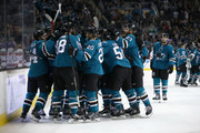 Brent Burns #88 of the San Jose Sharks is congratulated by teammates after he scored the game-winning goal on Cam Ward #30 of the Carolina Hurricanes in overtime at SAP Center on December 7, 2017 in San Jose, California.  (Photo by Ezra Shaw/Getty Images) *** Local Caption *** Brent Burns; Cam Ward
