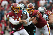 Quarterback Alex Smith #11 of the Washington Redskins is hit as he throws in the first quarter against the Carolina Panthers at FedExField on October 14, 2018 in Landover, Maryland.