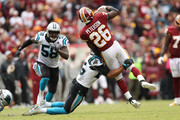 Running back Adrian Peterson #26 of the Washington Redskins is tackled by strong safety Eric Reid #25 of the Carolina Panthers in the fourth quarter at FedExField on October 14, 2018 in Landover, Maryland.
