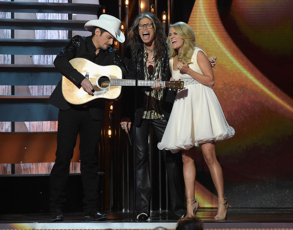 Carrie Underwood Brad Paisley, Steven Tyler, and Carrie Underwood speak onstage during the 48th annual CMA awards at the Bridgestone Arena on November 5, 2014 in Nashville, Tennessee.