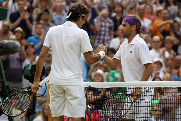 Roger Federer of Switzerland (L) shakes hands after winning against Arnaud Clement of France on Day Five of the Wimbledon Lawn Tennis Championships at the All England Lawn Tennis and Croquet Club on June 25, 2010 in London, England.