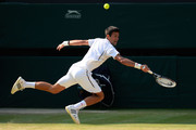 Novak Djokovic of Serbia stretches to play a backhand during the Gentlemen's Singles semi-final match against Juan Martin Del Potro of Argentina on day eleven of the Wimbledon Lawn Tennis Championships at the All England Lawn Tennis and Croquet Club on July 5, 2013 in London, England.