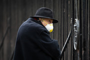 A man wearing a face mask watches as members of the Coldstream Guards prepare to march to Buckingham Palace on the day that Queen Elizabeth II is set to move to Windsor Palace in a bid to avoid the COVID-19 coronavirus pandemic on March 18, 2020 in London, England.
