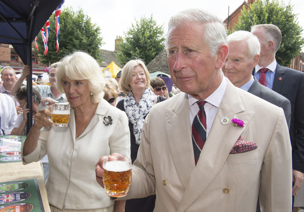 Charles, Prince of Wales and Camilla, Duchess of Cornwall try a taste of Rutland Bitter as they meets members of the local community and business owners on July 28, 2014 in Oakham, England. The Prince of Wales, as Patron of  'Step Up To Serve' met local young people involved in the campaign before visiting Oakham Castle, where The Duchess of Cornwall presented a decorative horse shoe to mark her first official visit to the town.