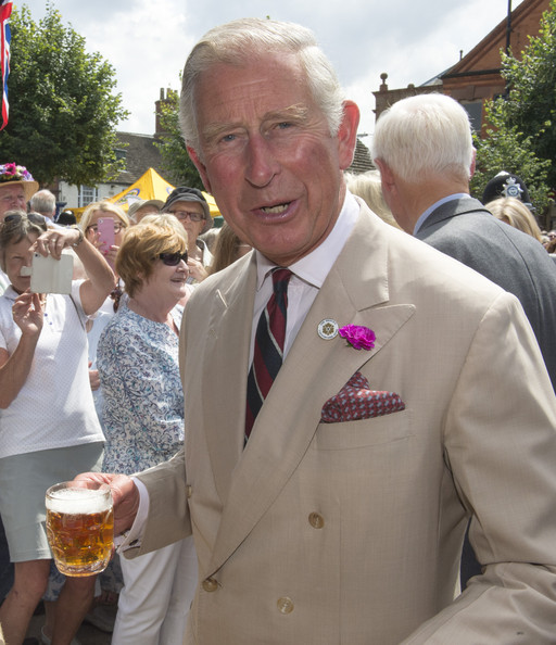 Charles, Prince of Wales trys a taste of Rutland Bitter as he meets members of the local community and business owners on July 28, 2014 in Oakham, England.
