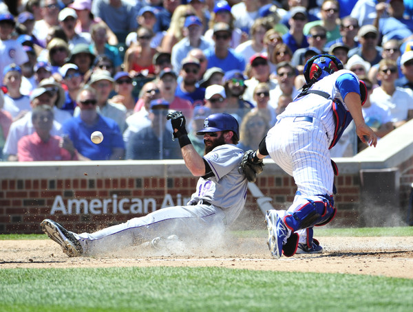 Charlie Blackmon scores as the throw gets away from Cubs' catcher David Ross.