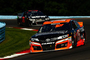 Clint Bowyer, driver of the #15 RK Motors Charlotte Toyota, leads Martin Truex Jr., driver of the #78 Furniture Row Chevrolet, during the NASCAR Sprint Cup Series Cheez-It 355 at Watkins Glen International on August 10, 2014 in Watkins Glen, New York.