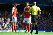 Referee Mike Dean prepares for showing a second yellow card to Gabriel of Arsenal during the Barclays Premier League match between Chelsea and Arsenal at Stamford Bridge on September 19, 2015 in London, United Kingdom.