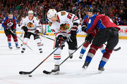 Kris Versteeg #23 of the Chicago Blackhawks controls the puck against Jan Hejda #8 of the Colorado Avalanche at Pepsi Center on November 26, 2014 in Denver, Colorado.