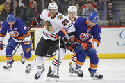 Andreas Martinsen #29 of the Chicago Blackhawks battles Josh Bailey #12 of the New York Islanders for position during the first period at the Barclays Center on March 24, 2018 in the Brooklyn borough of New York City.