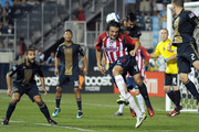Danny Califf #4 of the Philadelphia Union jumps over Miguel Ponce #4 of Chivas de Guadalajara to deflect the ball away from the goal at PPL Park on September 1, 2010 in Chester, Pennsylvania.