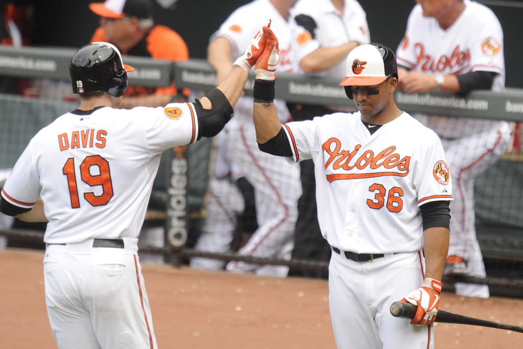 Chris Davis #19 of the Baltimore Orioles celebrates scoring a run in seventh inning with Chris Dickerson #36 during a baseball game on June 2, 2013 at Oriole Park at Camden Yards in Baltimore, Maryland.