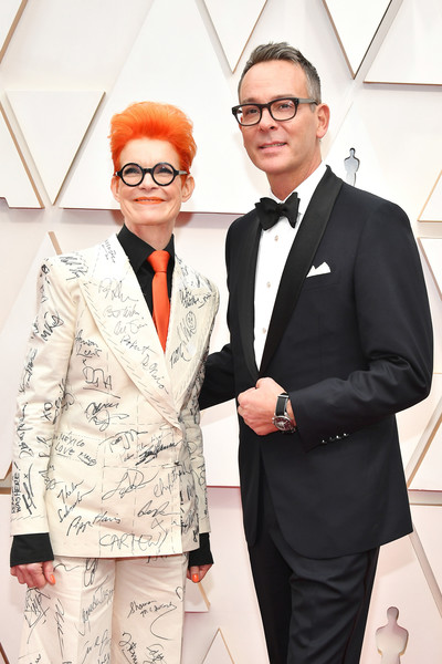 92nd Annual Academy Awards - Arrivals [yellow,red,fashion,suit,fashion design,human,eyewear,formal wear,event,outerwear,arrivals,sandy powell,christopher peterson,l-r,hollywood,california,highland,92nd annual academy awards,antonio banderas,pain and glory,red carpet,pen\u00e9lope cruz,92nd academy awards,academy award for best actor,academy award for best international feature film,actor,goya awards]