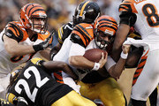 Bruce Gradkowski #7 of the Cincinnati Bengals hangs onto his teammate while being tackled by the Pittsburgh Steelers defense during the game on December 4, 2011 at Heinz Field in Pittsburgh, Pennsylvania.