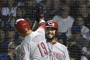 Joey Votto #19 of the Cincinnati Reds is greeted by Eugenio Suarez #7 after hitting a home run against the Chicago Cubs during the fourth inning on September 14, 2018 at Wrigley Field  in Chicago, Illinois.
