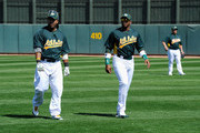 Outfielder Yoenis Cespedes #52 of the Oakland Athletics (C) and designated hitter Manny Ramirez #1 (L) warm up before the start of a spring training baseball game against the Cincinnati Reds at the Phoenix Municipal Stadium on March 10, 2012 in Phoenix, Arizona.