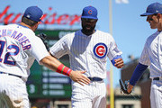 Jason Heyward #22 of the Chicago Cubs is congratulated by Kyle Schwarber #12 and Anthony Rizzo #44 after making a diving catch against the Cincinnati Reds at Wrigley Field on July 6, 2018 in Chicago, Illinois. The Reds defeated the Cubs 3-2.