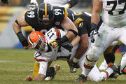 Jason Campbell #17 of the Cleveland Browns fumbles the ball while being tackled by Cameron Heyward #97 and Brett Keisel #99 of the Pittsburgh Steelers during the game on December 29, 2013 at Heinz Field in Pittsburgh, Pennsylvania.