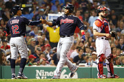 Blake Swihart #23 of the Boston Red Sox looks on as Edwin Encarnacion #10 high fives Francisco Lindor #12 of the Cleveland Indians after hitting a two-run home run in the fifth inning of a game at Fenway Park on August 22, 2018 in Boston, Massachusetts.