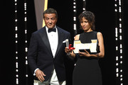 """Sylvester Stallone presents Mati Diop with the Grand Prix award for her film """"Atlantique"""" at the Closing Ceremony during the 72nd annual Cannes Film Festival on May 25, 2019 in Cannes, France."""