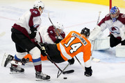 Sean Couturier #14 of the Philadelphia Flyers is hit by Erik Johnson #6 of the Colorado Avalanche during the second period at Wells Fargo Center on October 22, 2018 in Philadelphia, Pennsylvania.