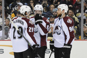 Nathan MacKinnon #29, Gabriel Landeskog #92 and Ryan O'Reilly #90 of the Colorado Avalanche talk before a faceoff in the second period at Consol Energy Center on December 18, 2014 in Pittsburgh, Pennsylvania.
