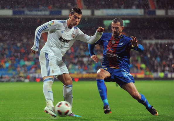 Cristiano Ronaldo Cristiano Ronaldo  (L) of Real Madrid crosses the ball before being tackled by Juanfran of Levante during the  La Liga match between Real Madrid and Levante at Estadio Santiago Bernabeu on February 19, 2011 in Madrid, Spain.
