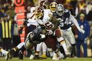 Running back Adrian Peterson #26 of the Washington Redskins breaks the tackle of defensive tackle David Irving #95 of the Dallas Cowboys in the fourth quarter at FedExField on October 21, 2018 in Landover, Maryland.