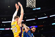 Deron Williams #8 of the Dallas Mavericks is fouled by Timofey Mozgov #20 of the Los Angeles Lakers in front of D'Angelo Russell #1 and Luol Deng #9 during the first half at Staples Center on December 29, 2016 in Los Angeles, California.  NOTE TO USER: User expressly acknowledges and agrees that, by downloading and or using this photograph, User is consenting to the terms and conditions of the Getty Images License Agreement.