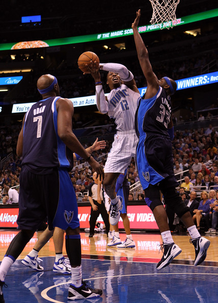 Dwight Howard #12 of the Orlando Magic attempts a shot against Brendan Haywood #33 of the Dallas Mavericks during the game at Amway Center on March 30, 2012 in Orlando, Florida.  NOTE TO USER: User expressly acknowledges and agrees that, by downloading and or using this photograph, User is consenting to the terms and conditions of the Getty Images License Agreement.