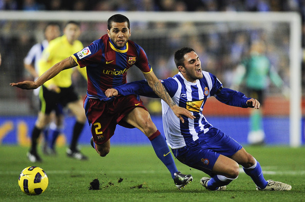 Daniel Alves Dani Alves of Barcelona (L) and Victor Ruiz of Espanyol duel for a ball during the La Liga match between Espanyol and Barcelona at Cornella - El Prat stadium on December 18, 2010 in Barcelona, Spain. Barcelona won the match 1-5.