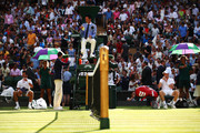 (L-R) Novak Djokovic of Serbia and Kyle Edmund of Great Britain take a break in play in their Men's Singles third round match on day six of the Wimbledon Lawn Tennis Championships at All England Lawn Tennis and Croquet Club on July 7, 2018 in London, England.