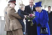 Alfie Lun, 2, is held up by his mother Michelle as he hands a bouquet to Queen Elizabeth II during the unveiling of the new memorial to members of the armed services who served and died in the wars in Iraq and Afghanistan at Victoria Embankment Gardens on March 8, 2017 in London, England.