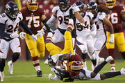 Running back Adrian Peterson #26 of the Washington Redskins is tackled by defensive back Tramaine Brock #22 of the Denver Broncos in the first quarter during a preseason game at FedExField on August 24, 2018 in Landover, Maryland.