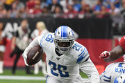 CJ Anderson #26 of the Detroit Lions runs the ball through a diving tackle by Clinton McDonald #93 of the Arizona Cardinals during the second quarter at State Farm Stadium on September 08, 2019 in Glendale, Arizona.