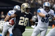 C.J. Spiller #28 of the New Orleans Saints is pursued by Travis Lewis #50 of the Detroit Lions during the first half of a game at the Mercedes-Benz Superdome on December 21, 2015 in New Orleans, Louisiana.