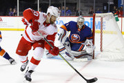 Henrik Zetterberg #40 of the Detroit Red Wings backhand sthe puck in front of Thomas Greiss #1 of the New York Islanders during the third period at the Barclays Center on December 19, 2017 in the Brooklyn borough of New York City. The Red Wings defeated the Islanders 6-3.