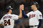 Logan Forsythe #24 and Joe Mauer #7 of the Minnesota Twins celebrate scoring against the Detroit Tigers during the third inning of the game on September 27, 2018 at Target Field in Minneapolis, Minnesota.