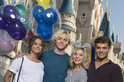 "In this handout photo provided by Disney Parks, (L-R) Actors Maia Mitchell, Ross Lynch, Grace Phipps and Garrett Clayton from the new Disney Channel film ""Teen Beach 2"" pose in front of Cinderella Castle during the 24-hour kick off to the 'Coolest Summer Ever' at Magic Kingdom Park at Walt Disney Resort on May 22, 2015 in Lake Buena Vista, Florida.  Magic Kingdom is one of four theme parks at Walt Disney World Resort in Lake Buena Vista, Florida."