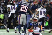 Kyle Arrington #25 helps teammate  Darrelle Revis #24 of the New England Patriots up after a touchdown by  Steve Smith #89 of the Baltimore Ravens in the first quarter during the 2014 AFC Divisional Playoffs game at Gillette Stadium on January 10, 2015 in Foxboro, Massachusetts.
