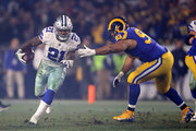 Ezekiel Elliott #21 of the Dallas Cowboys runs with the ball against Ndamukong Suh #93 of the Los Angeles Rams in the first half in the NFC Divisional Playoff game at Los Angeles Memorial Coliseum on January 12, 2019 in Los Angeles, California.