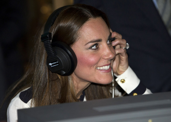 Catherine, Duchess Of Cambridge listens to a morse code message using a replica radio, with event manager Steve Lumby, during a tour the of the restored WWII Codebreaking Huts at Bletchley Park on June 18, 2014 in Bletchley, England. The pre-fabricated wooden huts that housed the secret Government code breaking school during WWII, where encrypted messages sent by the Navy, Army and Air Forces of Germany and its allies were decrypted, translated and analysed for vital intelligence, have undergone a year long restoration.