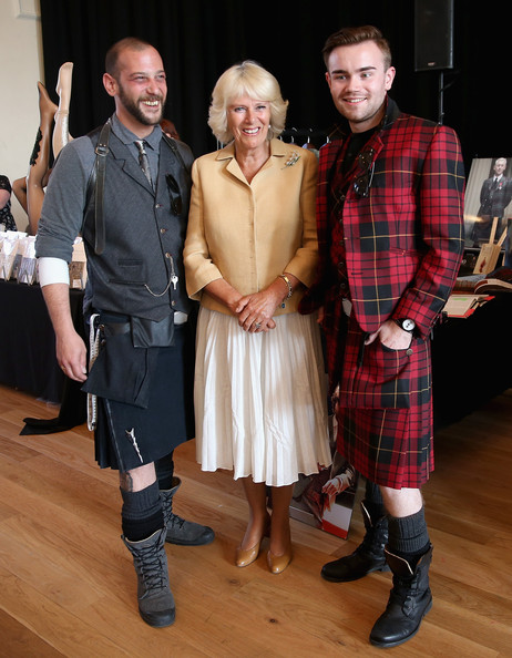 Camilla, poses with men in kilts as she browses stalls at the Fashion Festival in the Assembly Rooms on July 22, 2014 in Edinburgh, Scotland.