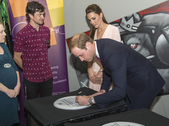 Nick O'Connor and Catherine, Duchess of Cambridge look on as Prince William, Duke of Cambridge signs a drum skin during their visit to the youth community centre, The Northern Sound System, in Elizabeth on April 23, 2014 in Adelaide, Australia. The Duke and Duchess of Cambridge are on a three-week tour of Australia and New Zealand, the first official trip overseas with their son, Prince George of Cambridge.