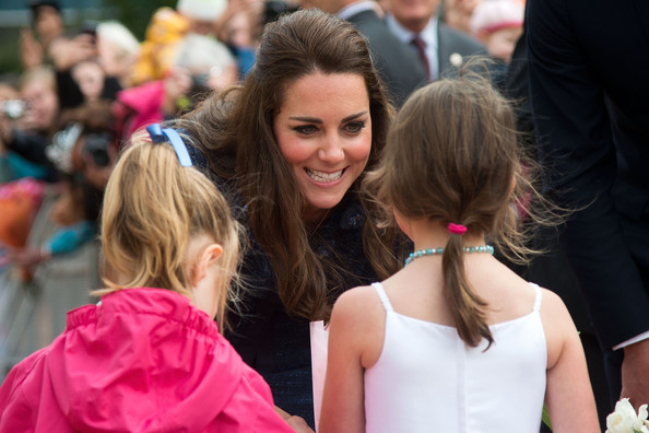 Catherine, Duchess of Cambridge speaks to two flower girls during a walk about in Civic Square on April 16, 2014 in Wellington, New Zealand. The Duke and Duchess of Cambridge are on a three-week tour of Australia and New Zealand, the first official trip overseas with their son, Prince George of Cambridge.