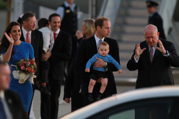 Catherine, Duchess of Cambridge (L) waves to the crowd as Prince William, Duke of Cambridge carries Prince George of Cambridge as he speaks to Sir Peter Cosgrove, Govenor General of Australia at Fairbairn Airport on April 20, 2014 in Canberra, Australia. The Duke and Duchess of Cambridge are on a three-week tour of Australia and New Zealand, the first official trip overseas with their son, Prince George of Cambridge.