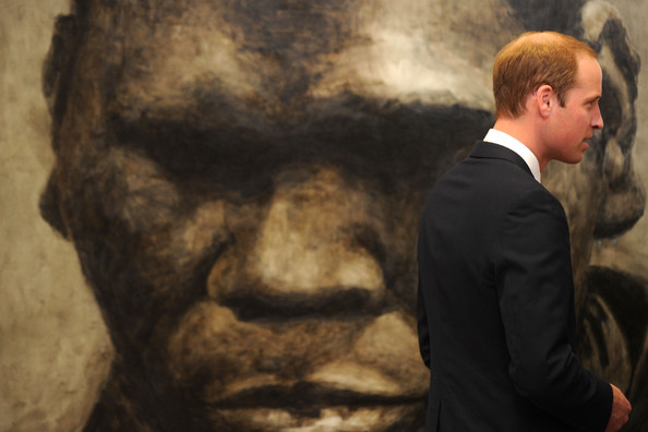 Prince William, Duke of Cambridge stands in front of a portrait of Australian musician Geoffrey Gurrumul Yunupingu during a visit the National Portrait Gallery on April 24, 2014 in Canberra, Australia. The Duke and Duchess of Cambridge are on a three-week tour of Australia and New Zealand, the first official trip overseas with their son, Prince George of Cambridge.