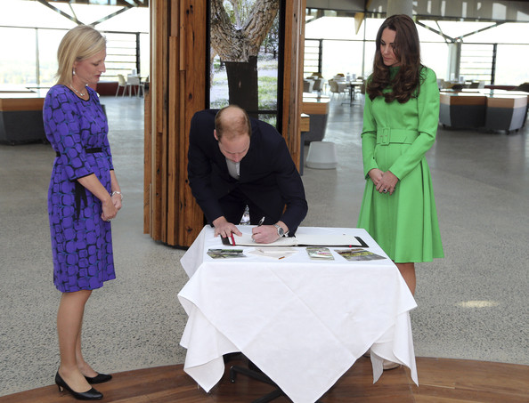 Prince William, Duke of Cambridge (C) and Catherine, Duchess of Cambridge (R) sign the visitors book as Katy Gallagher, Chief Minister of the Capital Territory (L) looks on during a visit to National Arboretum on April 24, 2014 in Canberra, Australia. The Duke and Duchess of Cambridge are on a three-week tour of Australia and New Zealand, the first official trip overseas with their son, Prince George of Cambridge.