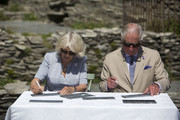 Prince Charles, Prince of Wales and Camilla, Duchess of Cornwall sign their names on slates that will be incorporated into Tintagel bridge during their visit to Cornwall, south west England on July 20, 2020 in Tintagel, England.